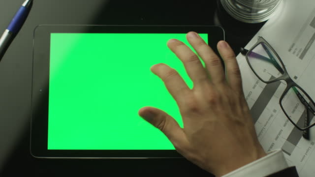 Businessman Using Tablet PC with Green Screen which Lying on the Table. Top view. Businessman Using Tablet PC with Green Screen which Lying on the Table. Top view. Shot on RED Digital Cinema Camera in 4K. pinching stock videos & royalty-free footage