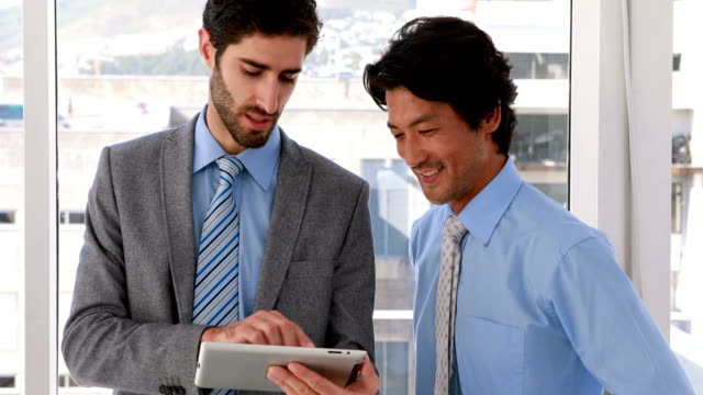 Businessman using tablet pc with his colleague video