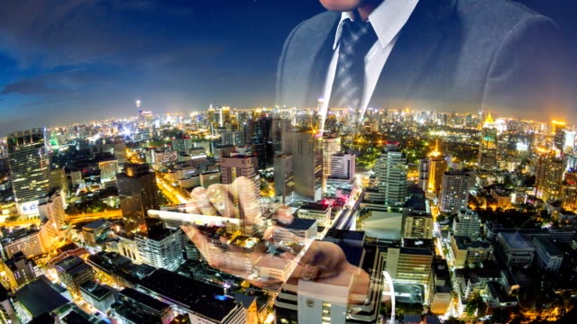 Businessman using tablet with cityscape in the night. video