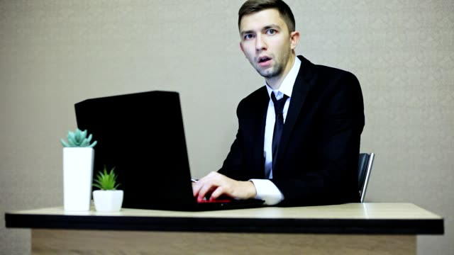 Businessman very surprised and looking at the camera while working at a laptop in the office