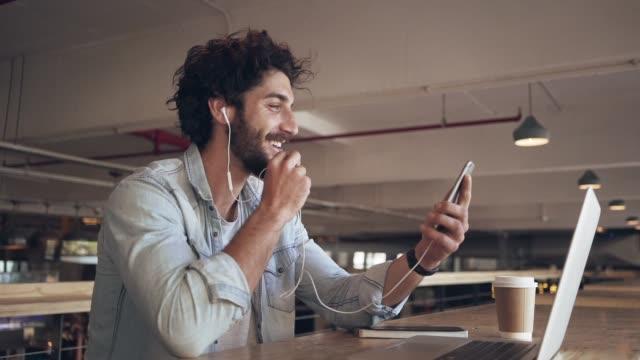 iş işadamı video arama üzerinde cellphone içinde cafe - kulaklık seti ses ekipmanı stok videoları ve detay görüntü çekimi