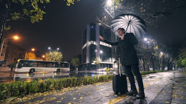 Businessman waiting for taxi or uber in the rain. video
