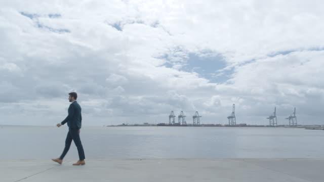 Businessman Walking Along Docks