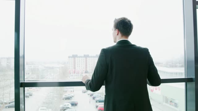 Businessman walking and stopping at office window, real time