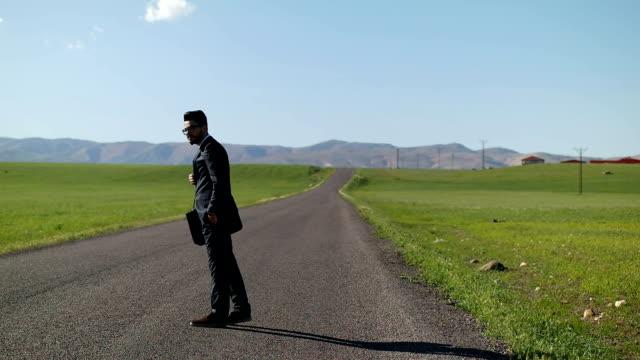 Businessman walking down curving rural road video