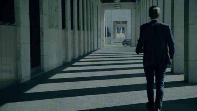 Geschäftsmann in einem columnade der Stadt – Video