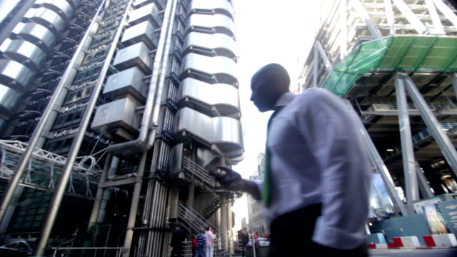 Businessman walking in business district of city video