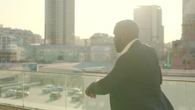 stockvideo's en b-roll-footage met zakenman die op stadsstraat loopt. bedrijfs mens die tijd op polshorloge controleert - afro amerikaanse etniciteit