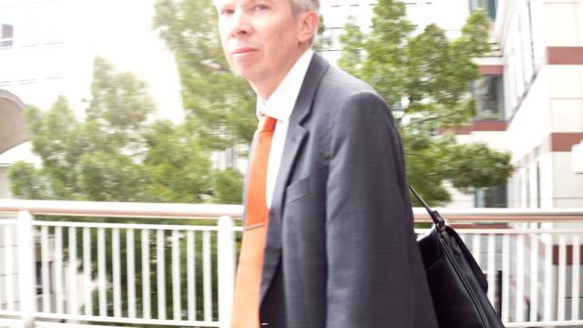 businessman walking past the camera - solo un uomo maturo video stock e b–roll