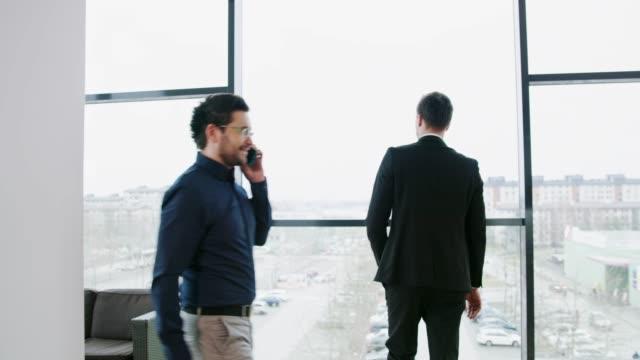 affärsman som gångavstånd till fönster i office, realtid - kameraåkning på räls bildbanksvideor och videomaterial från bakom kulisserna