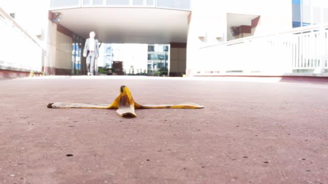 バナナスキンに向かって歩くビジネスマン - バナナ点の映像素材/bロール