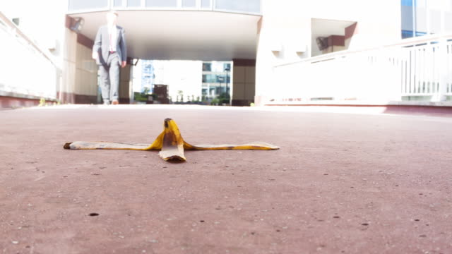 Businessman walking towards bananaskin Low angle view of a caucasian businessman stepping over a banana skin themes of accident insurance danger careless tripping falling stock videos & royalty-free footage