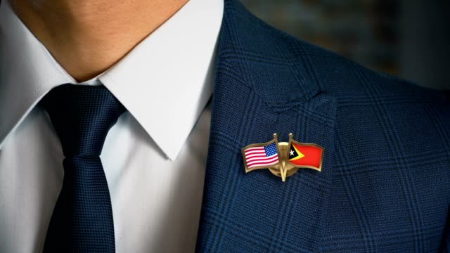 businessman walking towards camera with friend country flags pin united states of america - east timor.mov - politica e governo video stock e b–roll