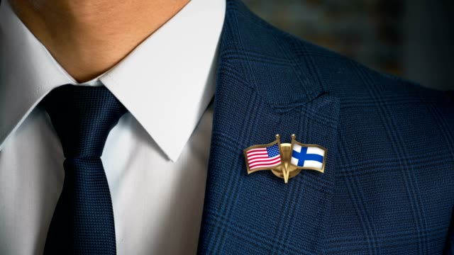 businessman walking towards camera with friend country flags pin united states of america - finland - holiday background стоковые видео и кадры b-roll