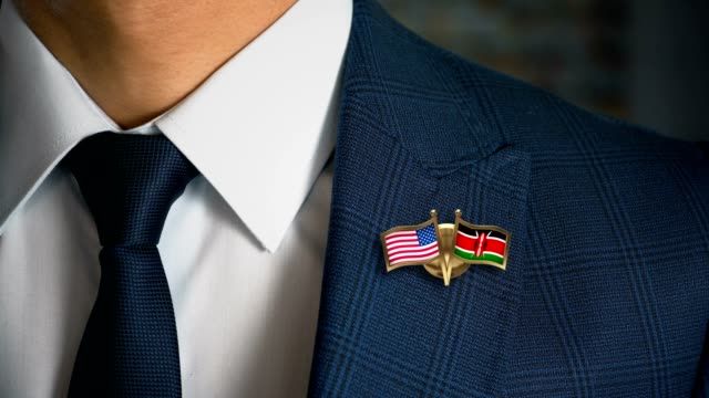 businessman walking towards camera with friend country flags pin united states of america - kenya.mov - holiday background стоковые видео и кадры b-roll
