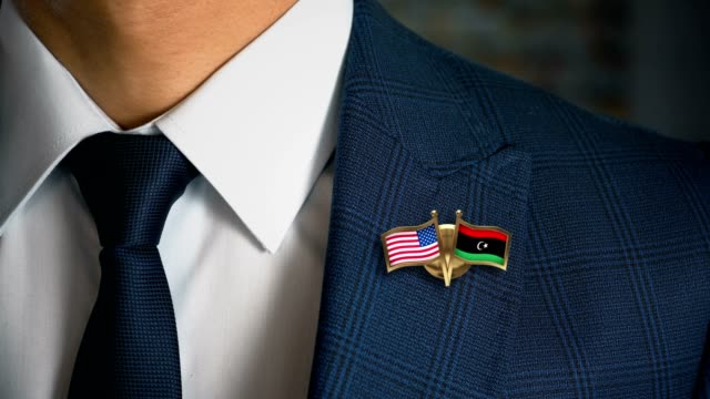 businessman walking towards camera with friend country flags pin united states of america - libya.mov - libia video stock e b–roll
