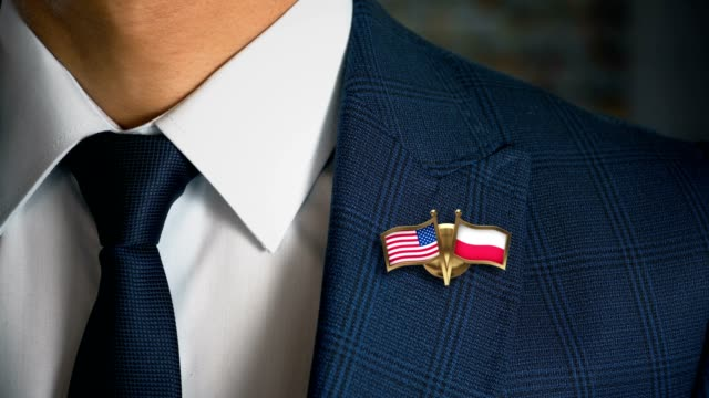 businessman walking towards camera with friend country flags pin united states of america - poland.mov - holiday background стоковые видео и кадры b-roll