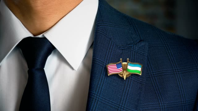 businessman walking towards camera with friend country flags pin united states of america - uzbekistan - holiday background стоковые видео и кадры b-roll