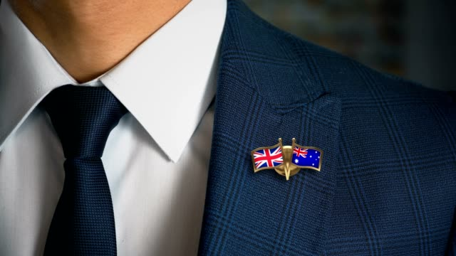 businessman walking towards camera with friend country flags pin united kingdom - australia.mov - badge video stock e b–roll