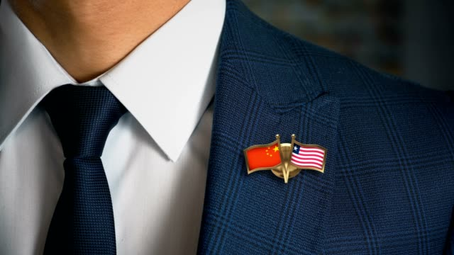 businessman walking towards camera with friend country flags pin china - liberia - liberia video stock e b–roll