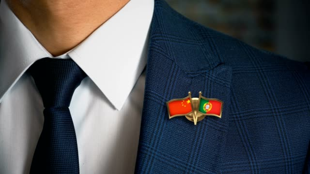 businessman walking towards camera with friend country flags pin china - portugal - holiday background стоковые видео и кадры b-roll