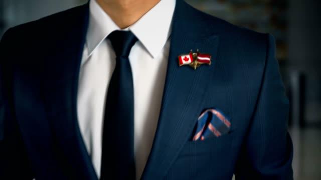 vídeos de stock, filmes e b-roll de empresário, caminhando em direção a câmera com amigo país bandeiras pin canadá - letónia - países bálticos