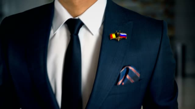 businessman walking towards camera with friend country flags pin belgium - russia - campionato video stock e b–roll