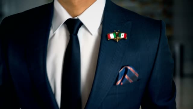 businessman walking towards camera with friend country flags pin italy - mexico - holiday background стоковые видео и кадры b-roll