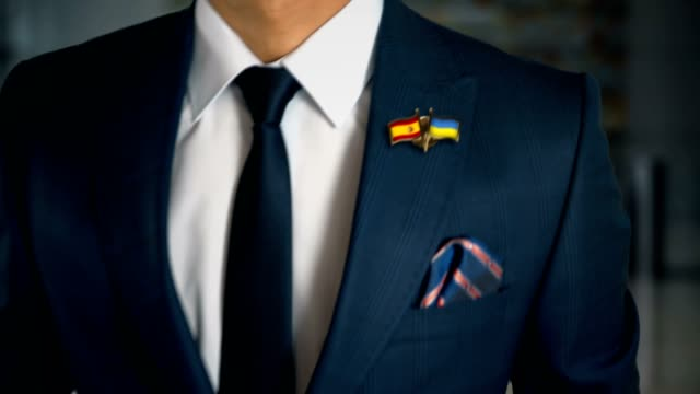 businessman walking towards camera with friend country flags pin spain - ukraine - holiday background стоковые видео и кадры b-roll