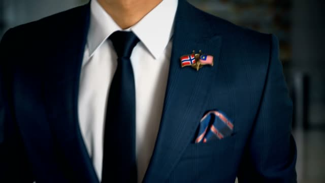 businessman walking towards camera with friend country flags pin norway - malaysia - holiday background стоковые видео и кадры b-roll
