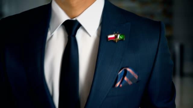 vídeos de stock e filmes b-roll de businessman walking towards camera with friend country flags pin poland - pakistan - badge