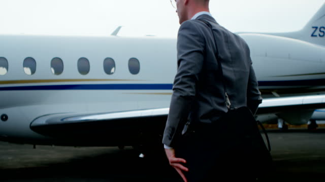 Businessman walking towards private jet 4k Businessman walking towards private jet on a runaway 4k military private stock videos & royalty-free footage