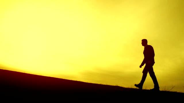 Businessman Walking Up a Hill toward top sun success concept video