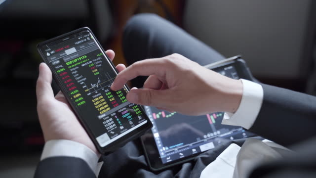 Businessman watching stock market on smart phone