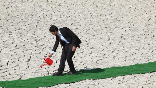 Businessman watering cracked earth via can video