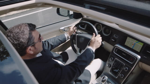 Businessman wearing a suit drives a car, sunroof shot - vídeo