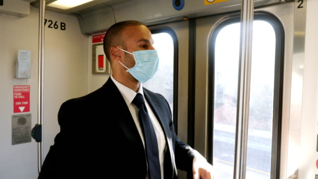 businessman wearing face mask rides train to work - businessman covid mask video stock e b–roll