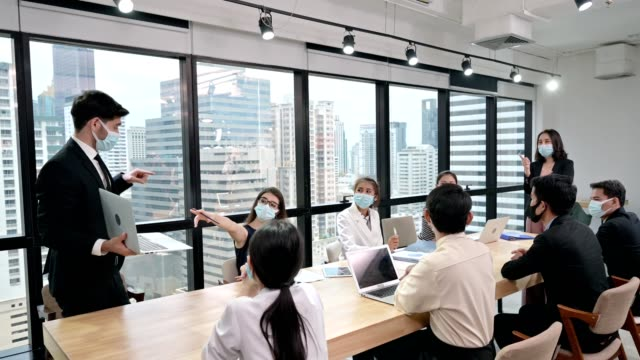 businessman wearing face mask with presentation of business plan on laptop. corporate business meeting in modern office - conferenza stampa video stock e b–roll