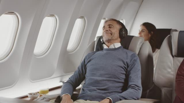 개인 제트기에서 헤드폰을 착용한 사업가 - airplane seat 스톡 비디오 및 b-롤 화면