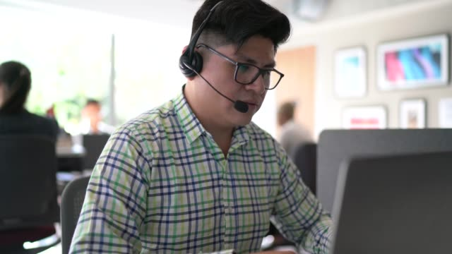 businessman wearing headsets while he's talking and working in office - rispondere video stock e b–roll