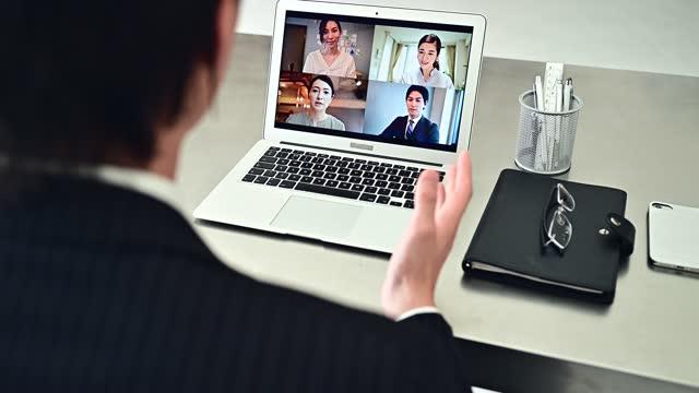 スーツを着たビジネスマンがオフィスでオンライン会議をしています - 人里離れた点の映像素材/bロール