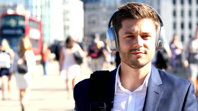 vídeos de stock, filmes e b-roll de homem de negócios usando fones de ouvido sem fio andando para o trabalho em câmara lenta - podcast