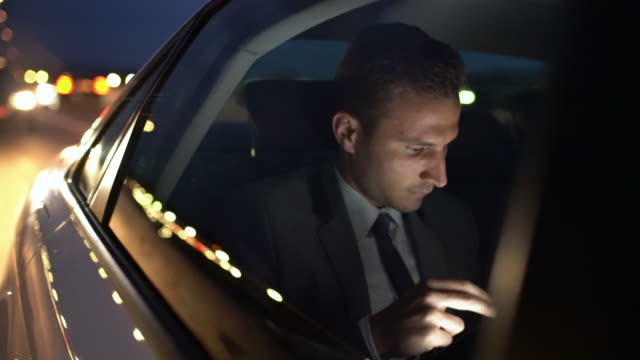 MS Businessman wind down a window of a limousine driving in the city at night video