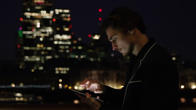 DS Businessman with a digital tablet in the city at night video