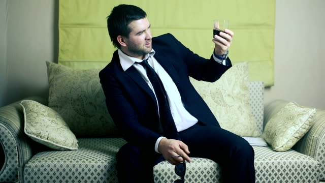 businessman with a glass of whiskey on the couch video