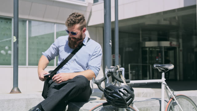 DS Businessman with beard using a smartphone in front of the office building video