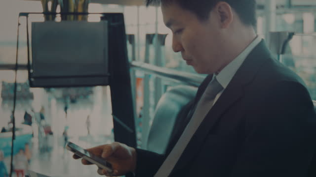 Businessman with cell phone at Station Businessman with cell phone at Station railroad station platform stock videos & royalty-free footage