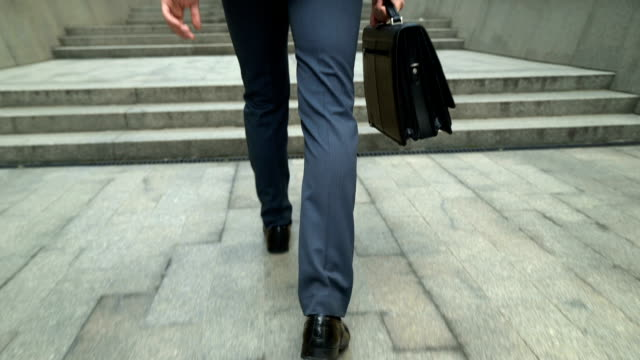 Businessman with diplomatic briefcase climbing stairs to office building, career