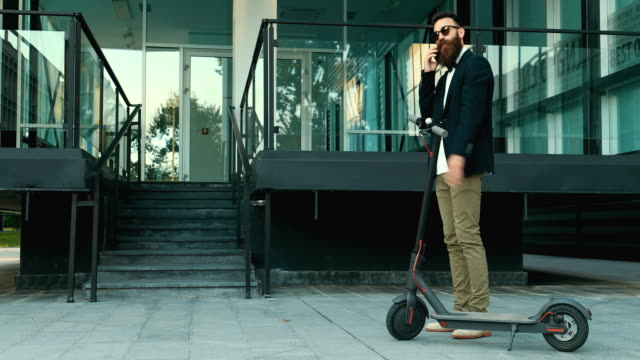 businessman with electric push scooter - monopattino elettrico video stock e b–roll