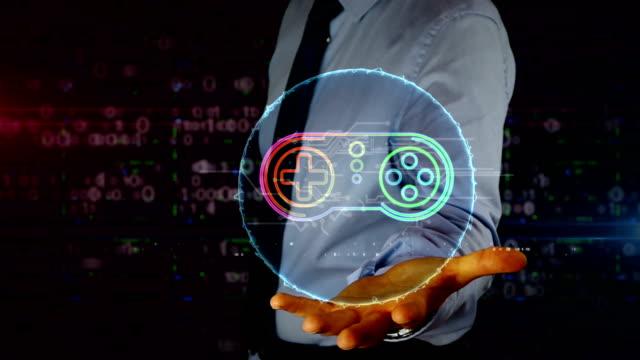 Businessman with game pad symbol hologram